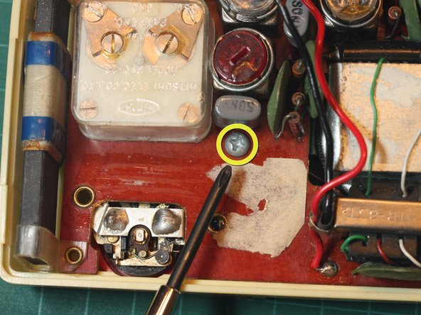 Image 1/1: Using a Phillips #1 screwdriver, remove the lone screw in the center holding the circuit board in place