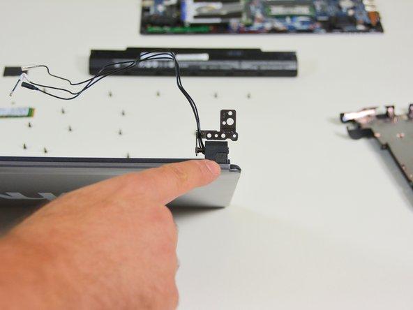 Image 3/3: Orten Sie die Schraubenabdeckung des rechten Scharniergelenkes.