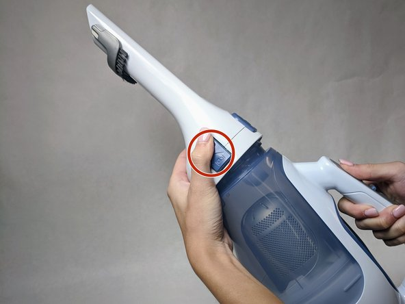 Press the buttons with unlock symbols on both sides of the nozzle.