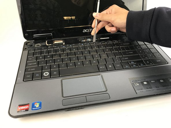 With the top panel remove, use the spudger to lift the keyboard out of the device as shown.