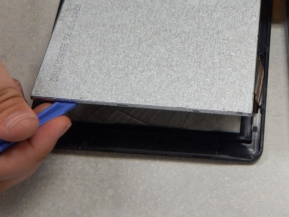 Use a separator tool to lift the screen from the port side of the casing and remove it.