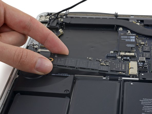 Image 2/3: Pull the SSD straight out of its socket on the logic board.