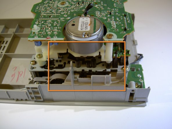 Image 1/3: Using fingers or tweezers, pull the indicated latch to the right to disconnect the tape player unit from the top of the device.