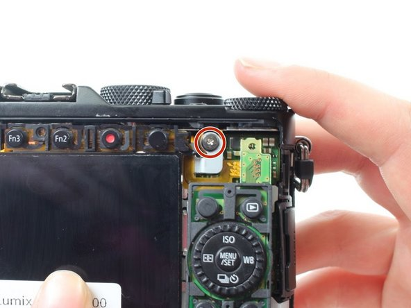 Use a Phillips #000 screwdriver to remove the 7.5mm screw on the top right of the back of the camera that holds the metal backing in place.