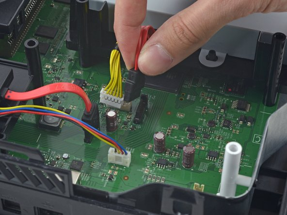 Disconnect the optical drive power and SATA data cables from the motherboard.
