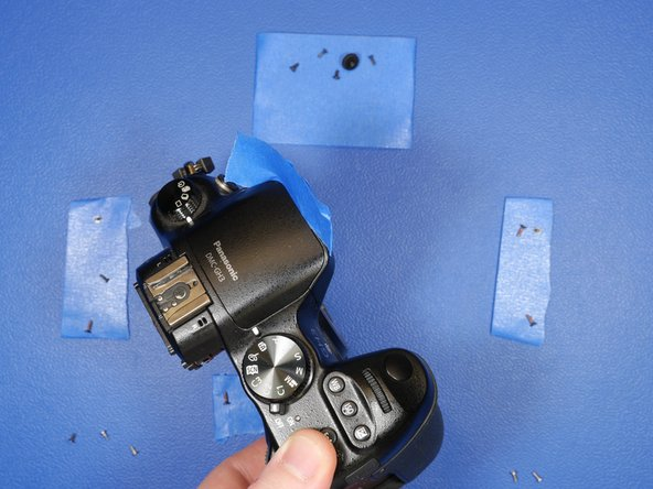 I discovered an easy solution. Take a piece of blue tape, fold it over and shove it between the flash assembly and the shell of the camera.