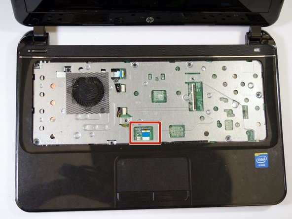 Locate the ribbon cable just above the touchpad.