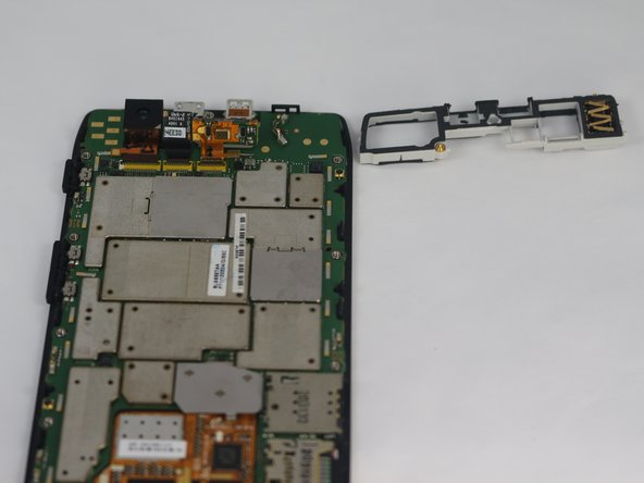 Image 3/3: Using the plastic opening tool, carefully pry the Antenna/Headphone Jack piece off the motherboard assembly.