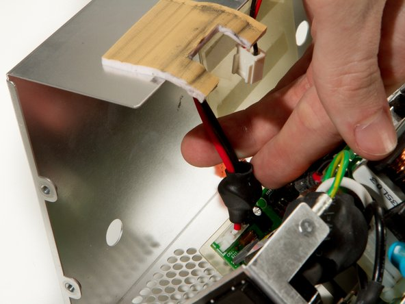 Carefully open the power supply, and be mindful of the cable that will be pulled taut that needs to be disconnected.