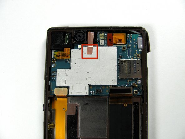 Image 1/3: Release the copper tape located at the top middle of the phone with a plastic opening tool. This will take some force since the adhesive is rather strong.