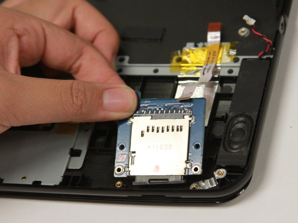 To reassemble, first insert the bottom of the SD card reader then carefully push downward.