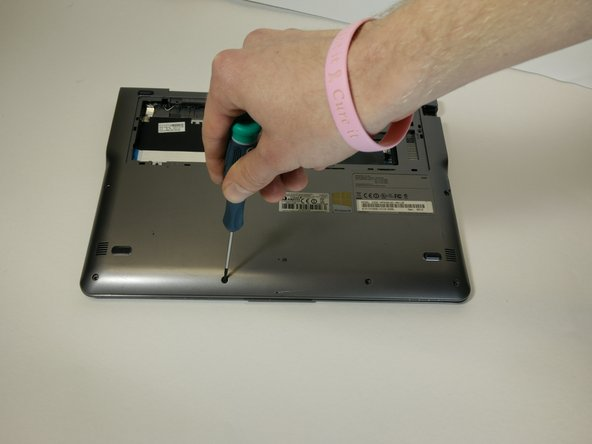 Image 2/2: Remove the screws holding the cover on from under the hard drive cover. These are 6.7 mm long.