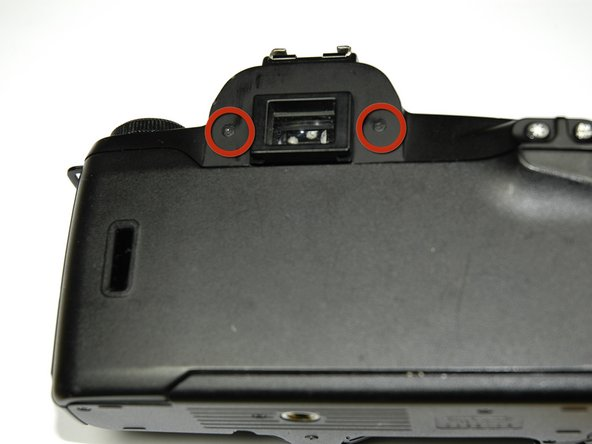 Image 1/1: Using a #00 Phillips screw driver, unscrew the two 4.9 mm Phillips screws located on either side of the viewfinder.