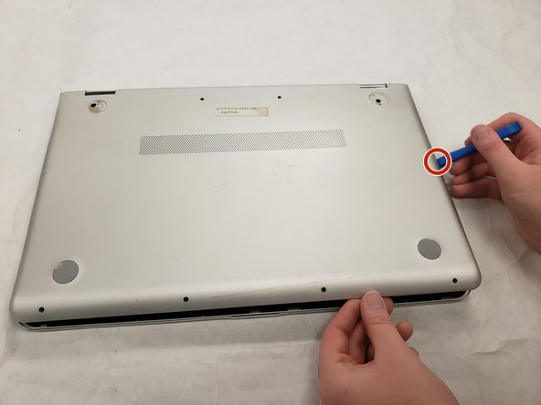 Insert the iFixit plastic opening tool between the bottom cover and bottom chassis.