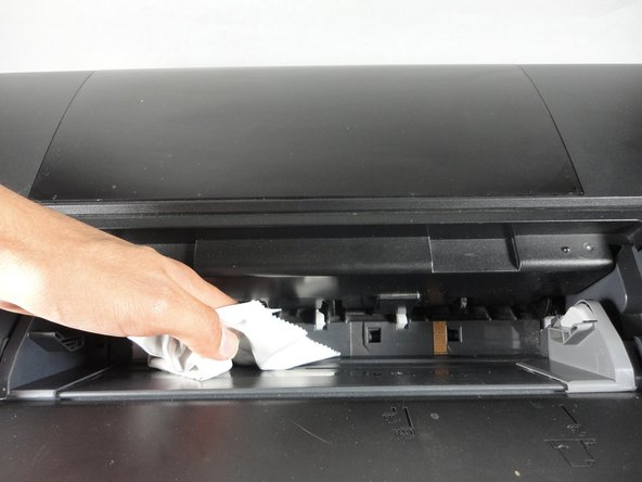 If there are ink spots or dirt on the inside of the printer, use cloth to clean the plastic area shown.