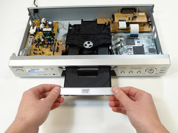 Remove the DVD tray lid by simultaneously pulling forward and lifting up on both corners firmly.