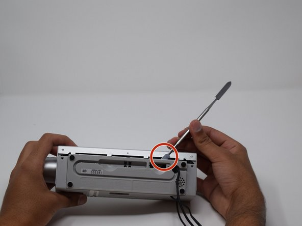 Using a thin flat tool, pry off the panel on the back of the device.