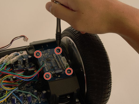 Using your Phillips #2 screwdriver, remove the four 8mm screws marked in red from the gyroscope.