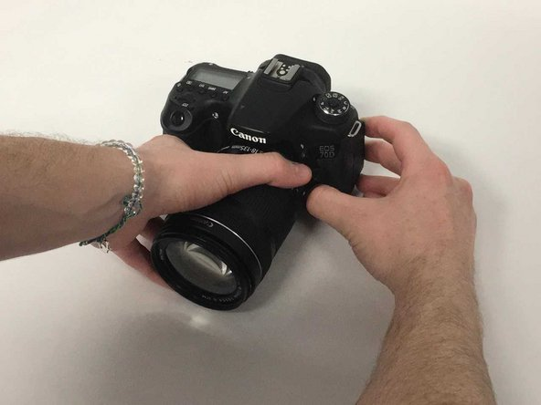 Next, grab the lens and rotate it counter-clockwise when looking at the camera.