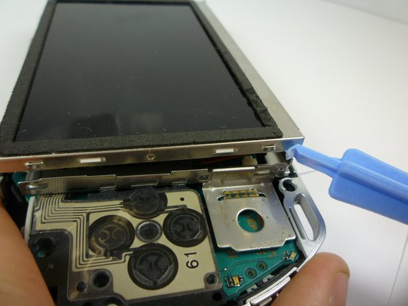 The LCD Screen is held by the LCD Frame with similar clips.  Slide a thin tool between the clip and the screen and gently pry them apart while beginning to lift the screen.