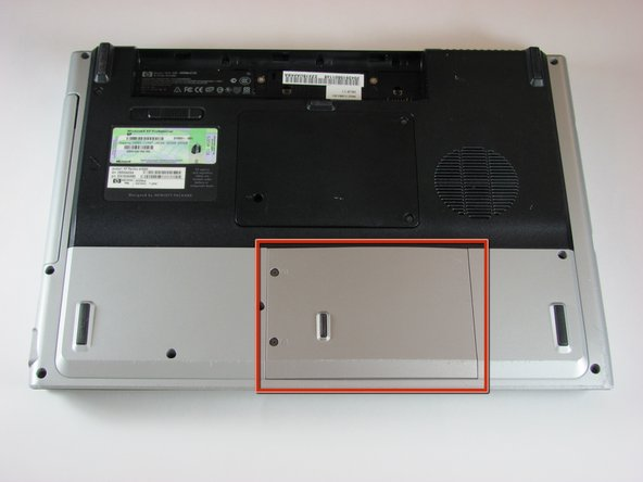 Locate the hard drive cover. Note that in this image, the RAM cover is still in place.
