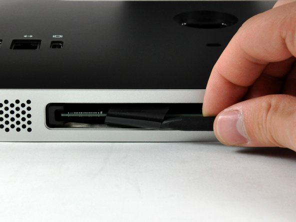 Image 1/2: Pull the black plastic RAM tab away from your iMac to eject the RAM chip.