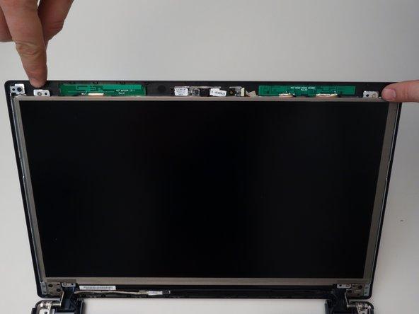 Repérez les 2 vis de fixations supérieures de l'écran LCD. Dévissez-les.