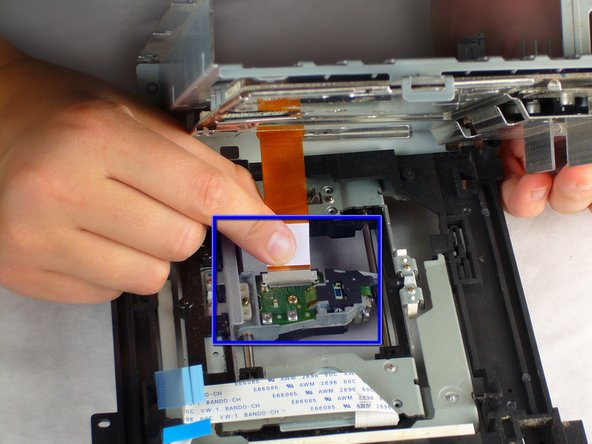 Carefully remove the orange ribbon cable from the laser by gently pulling on the white plastic strip.