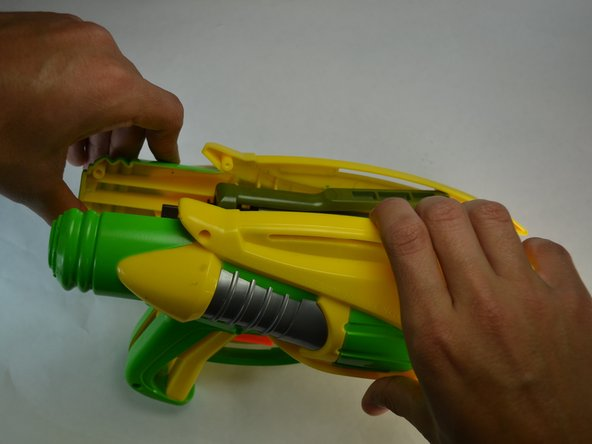 Using the plastic opening tools, carefully take apart the main case of the blaster to leave the inside exposed.