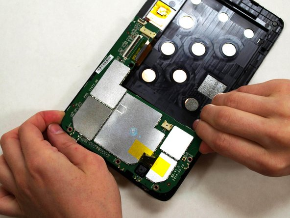 Holding the motherboard carefully by the edges, gently lift it up off the screen and carefully set it aside.