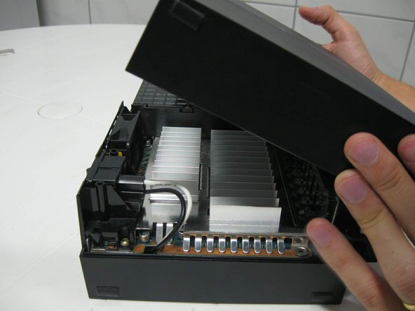 Put the console in the normal horizontal position, and pull the top cover from back to front.