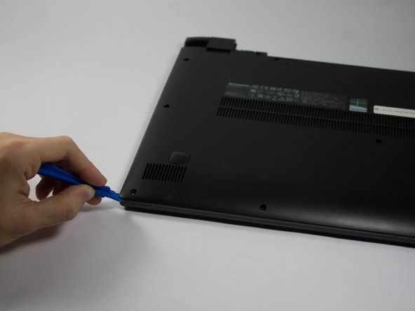 Using a plastic opening tool, make your way around the edge of the laptop.