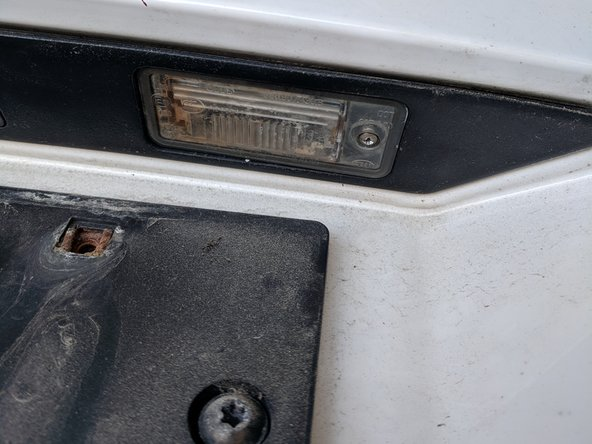 Open the hatchback and hold it in place so that you can easily reach the lights that illuminate the license plate. You may need to have another person hold the hatchback steady for you.