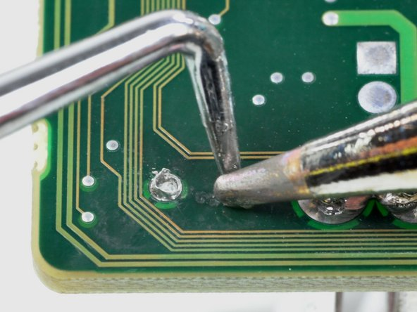 Image 1/2: Both solder holes should now be open enough to insert the bare leads of your component.
