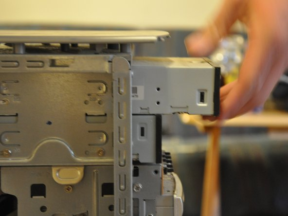 Gently pull the optical drive through the frontal cavity.