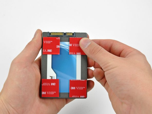 Peel the backing off one side of the double-sided tape and place the pieces at the four corners of the hard drive.