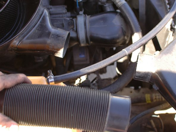 Remove the flexible hose that is between the air cleaner housing and the air intake nozzle above the passenger/right side headlight. It will contract enough to pull off.