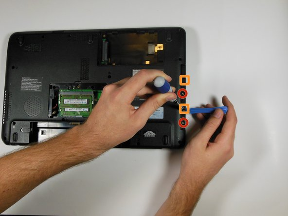 Image 1/1: Then use a Phillips #1 screwdriver and a plastic opening tool to undo the two tabs in this location.