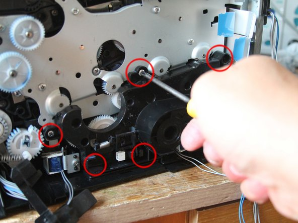 Als nächstes entfernen wir auch das Farbsteuerungsgetriebe (Schwarzes, großes Kunststoff-Bracket mit 15 in einandergreifenden Zahnrädern (5 Schrauben sind zu lösen