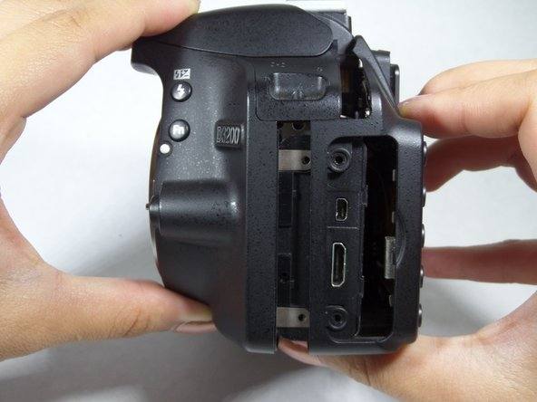 Image 1/2: Gently pull the back portion of the camera, one hand gripping the body and the other gripping the LCD screen.