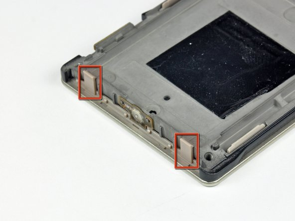 The five plastic clips along the side of the Zune lock onto small aluminum tabs cast into the inner chassis. To separate these clips, the plastic portion must be pushed toward the inside of the Zune while prying the inner chassis up off the front case.