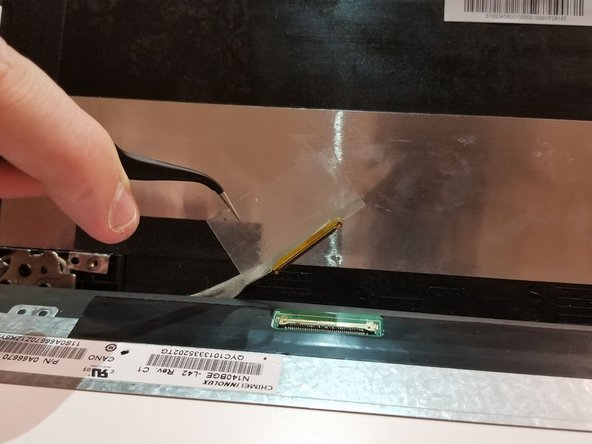 Peel up the adhesive tape to unlatch the metal retaining bracket on the display cable.