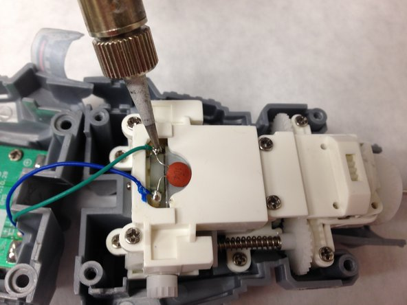 Use the soldering iron to remove the blue and green wire from the motor casing.  Directions on how to solder can be found here.