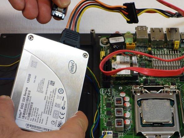Ziehen Sie den ersten Stecker der SSD Festplatte aus, indem Sie auf die Entriegelungsfeder drücken.