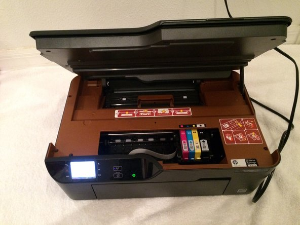 Lift up the lid to the printer using the notch on the right side of the printer to expose the ink cartridges.