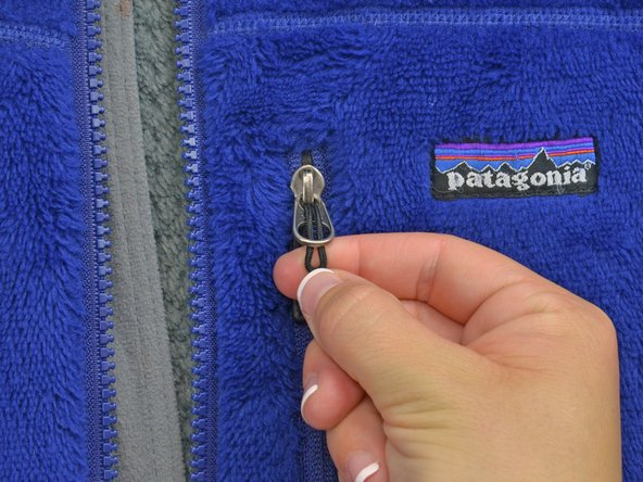 Image 2/2: Take top end of the zipper pull and insert it into the bigger, lower hole in the zipper.