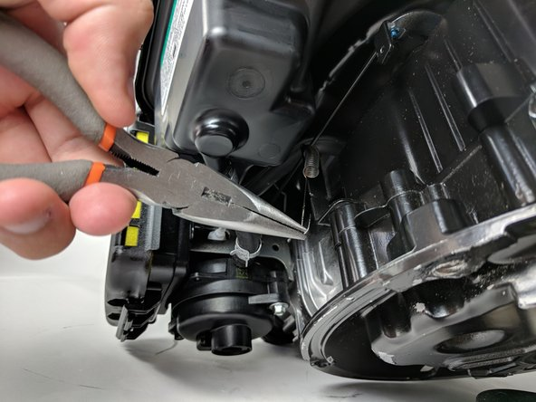 Using needle-nose pliers, carefully unhook the spring from the end opposite the air filter.