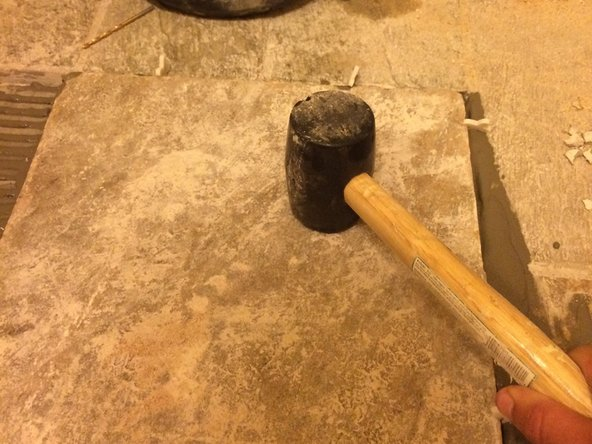 When hammering tile use enough force to sink the tile further into the mortar, but not enough to shatter the tile.