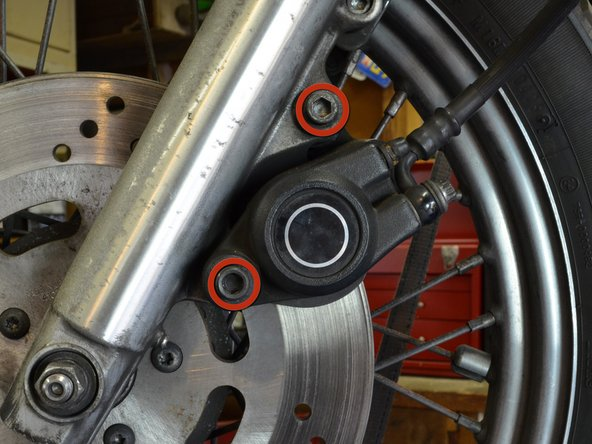"Using a 1/4"" hex head or allen wrench, unscrew the two bolts holding the front brake assembly to the fork."