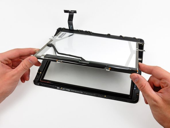 Image 1/2: Carefully peel the adhesive securing the long side of the LCD to the display frame, then remove the LCD.